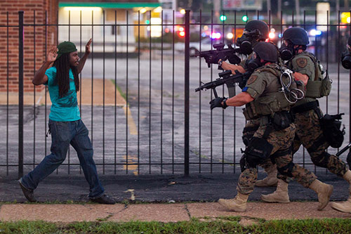 Rashaad Davis, 23, backs away as St. Louis County police officers approach him with guns drawn and eventually arrest him, Ferguson, Missouri, August 11, 2014